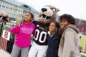 Three students stand with the Lafayette Leopard. The football field is in the background.